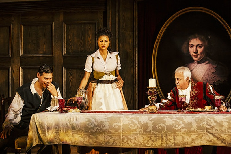 Vella Lovell, Brian George, and Ruy Iskandar in Witch by Jen Silverman directed by Marti Lyons at the Geffen Playhouse, 2019, Brian and Ruy around a banquet table, Vella stands with dishes between them