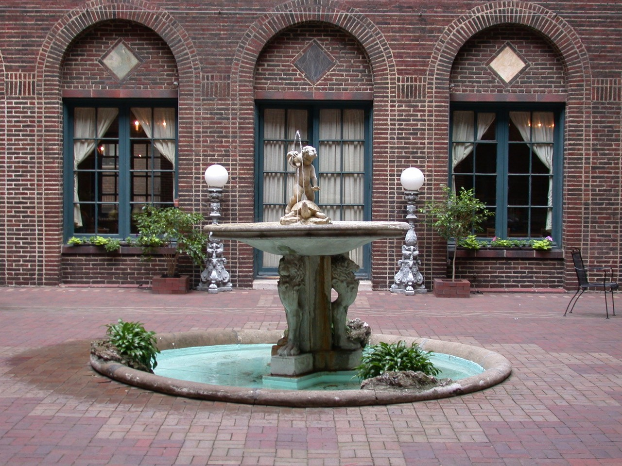Decorative fountain in the center of a brick patio with three arched windows in the background