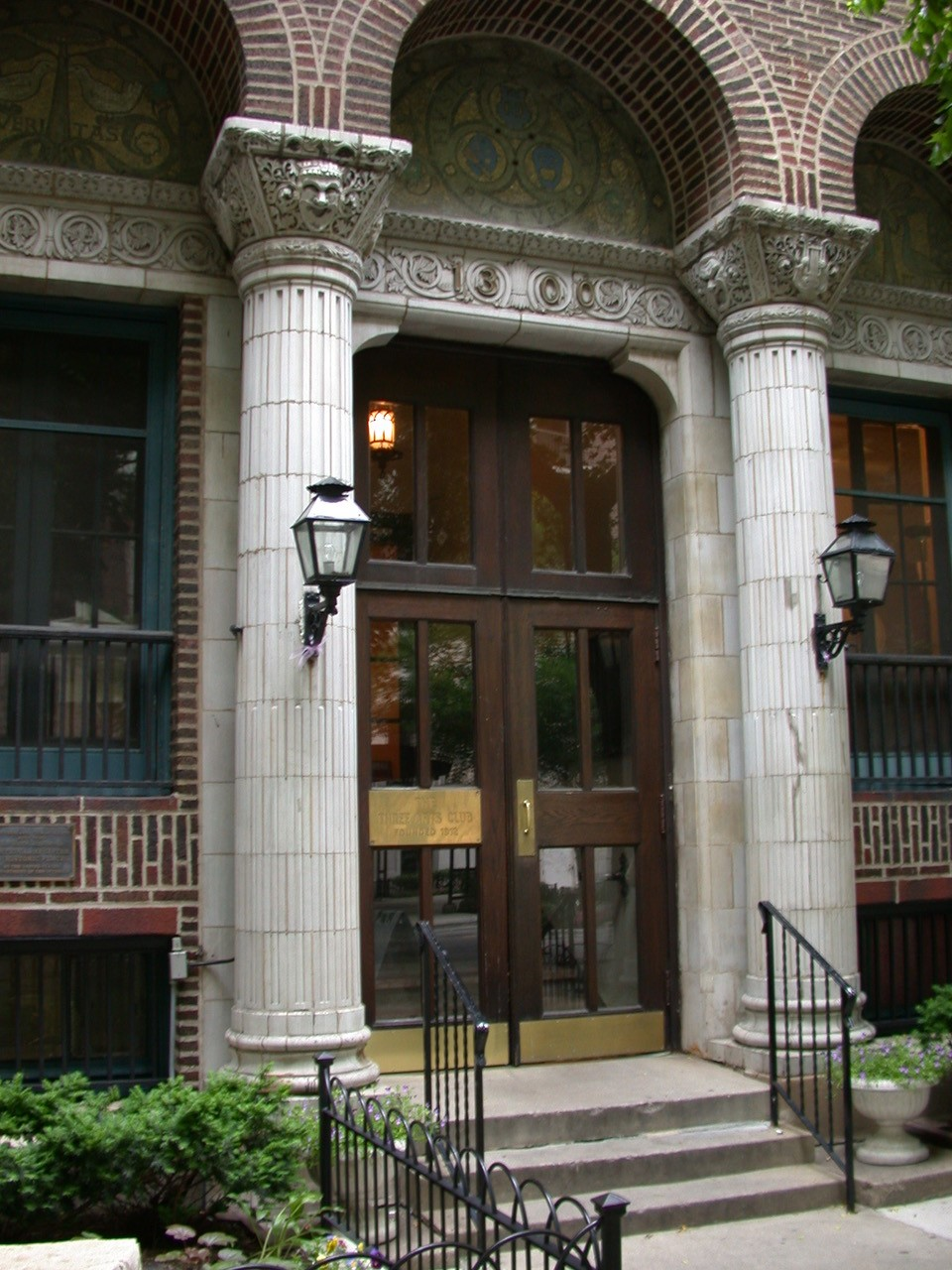 Image of wooden double doors flanked by decorative columns serving as the entrance to the Three Arts Club building